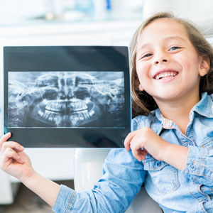 Little girl holding dental xray