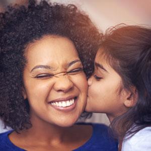 Little girl kissing mom on cheek
