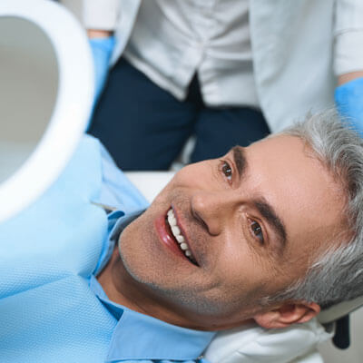 mature man sitting in dentist chair smiling