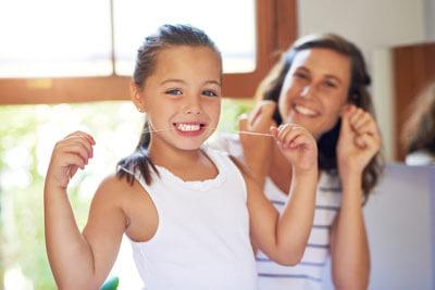 Girl flossing her teeth
