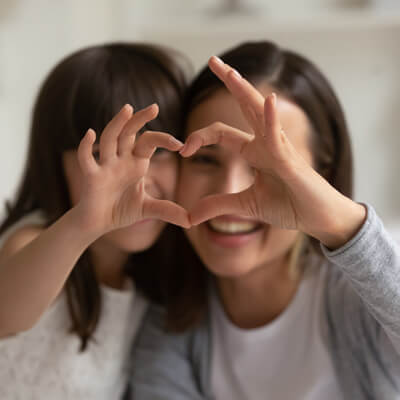 Girl and mom heart hands