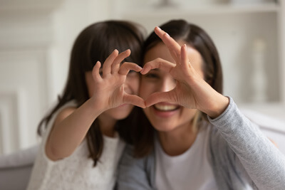 Mom and daughter making heart with hands