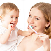 Mother and toddler brushing teeth together
