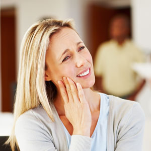 woman holding jaw in pain