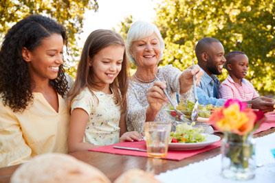 Multigeneration family eating together