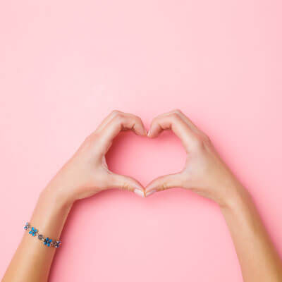 Hand making heart against pink wall