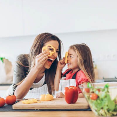 playful mom and daughter making salad