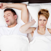 Man snoring and woman with pillow over ears
