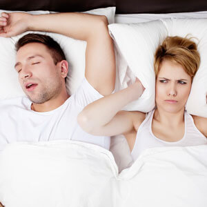 Woman covering her ears with a pillow while man snores