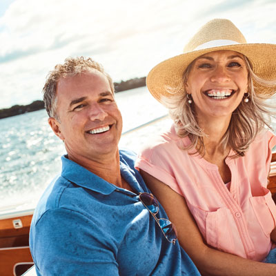 Older, smiling couple sitting in a boat