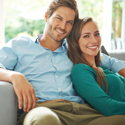 couple siting on couch smiling
