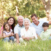 Multi-generational family sitting in the grass