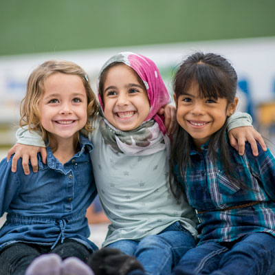 Three young girls hugging and smiling