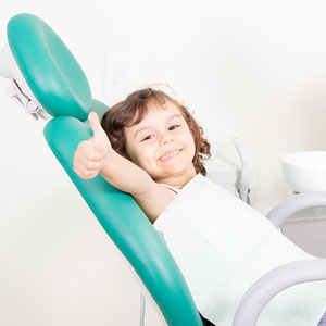 Thumbs up child on dental chair