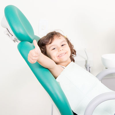 Little girl in dentist chair giving thumbs up