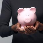 Woman in black shirt holding pink piggy bank