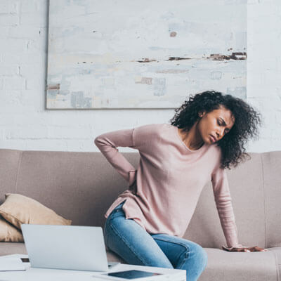 Woman leaning on sofa with back pain