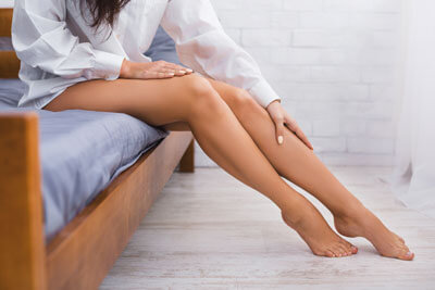 woman on bed with leg pain