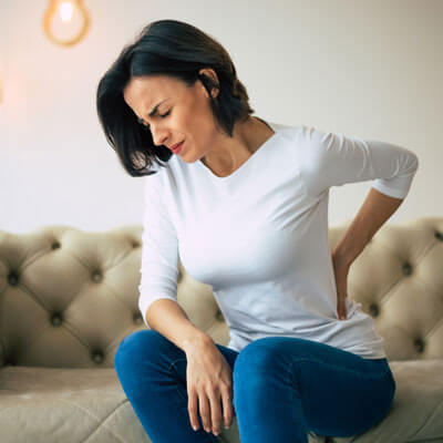 Woman on fancy couch with back pain