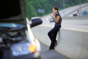 woman on the phone next to wrecked car