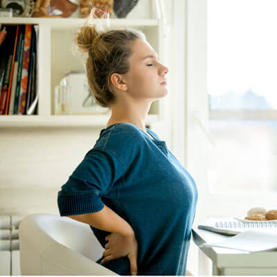 Woman with back pain in home office