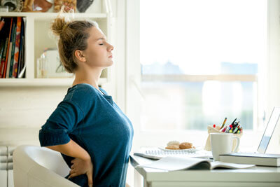 Woman with lower back pain at desk