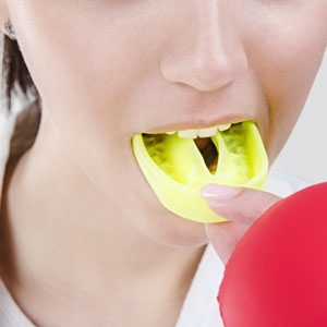 Woman inserting custom mouthguard