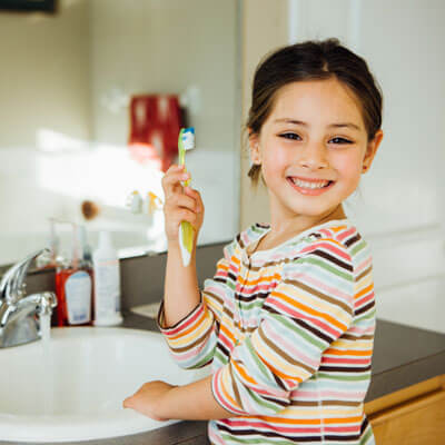 Young girl cleaning teeth at sink
