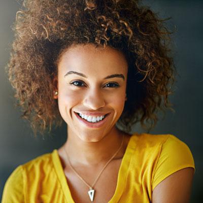 Woman with beautiful, white smile wearing yellow shirt