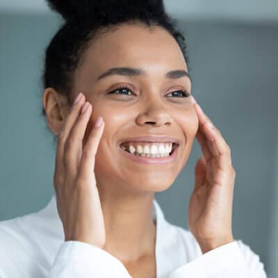 Young woman touching cheeks