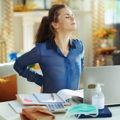 young woman working from home with back pain