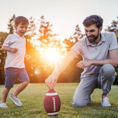 dad and son kicking football