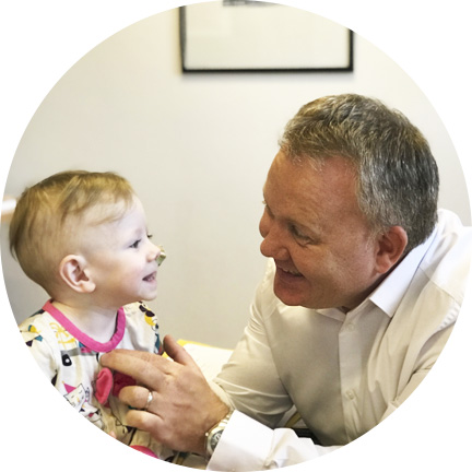 Chiropractor Dr Brian McElroy talking to little girl