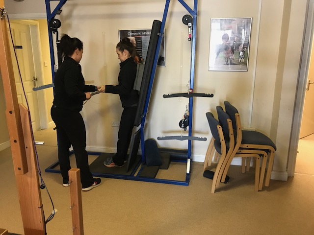 Gina instructing Angela in the use of the Standing Traction machine
