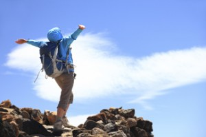 A person standing on a mountain top with their arms out-stretched.