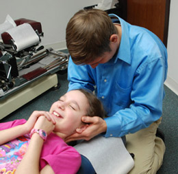 Dr. Lippert at {PRACTICE NAME} adjusting chiropractic patient.