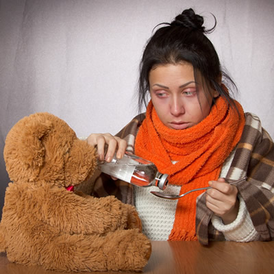 Woman with flu and bear toy