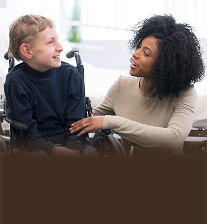 woman talking to boy in wheelchair