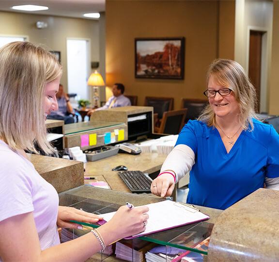 Staff handing paperwork to patient