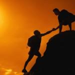 Two men climbing on mountain peak on sunset