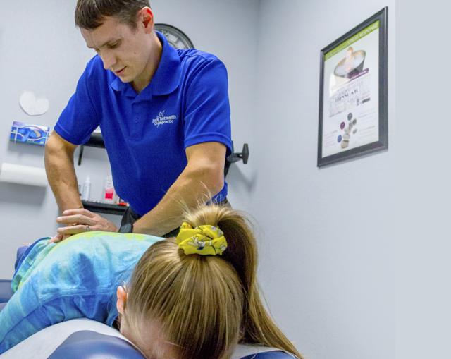 Dr. Derek Carroll adjusting patient