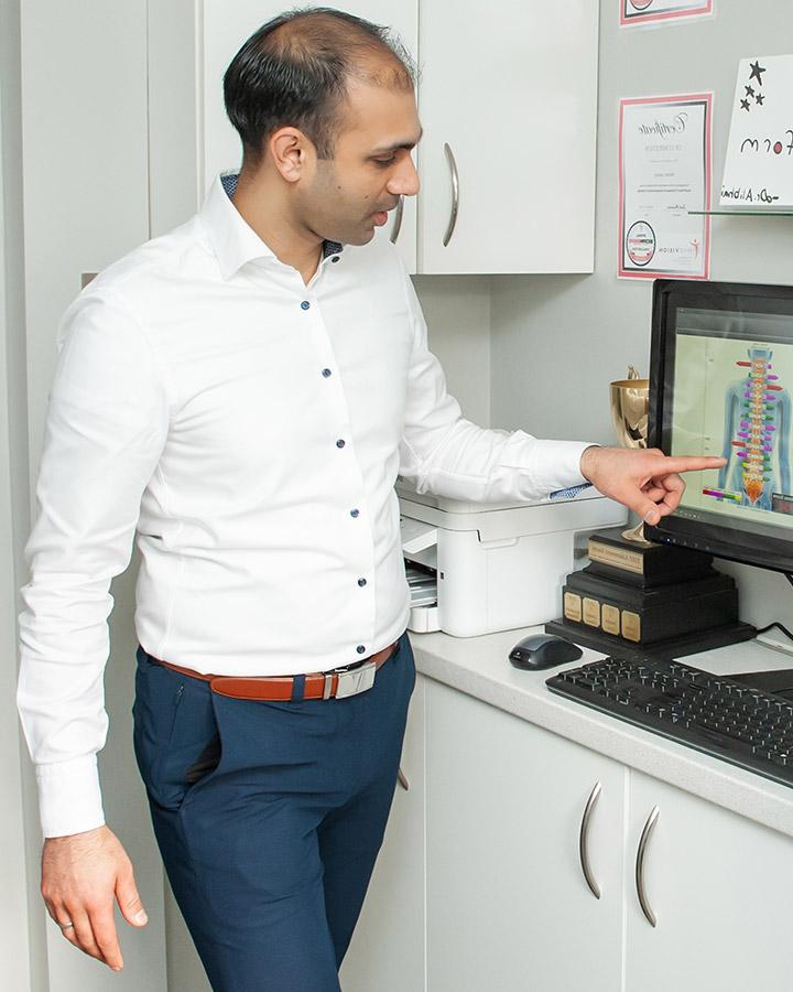 Dr. Alibhai pointing at computer