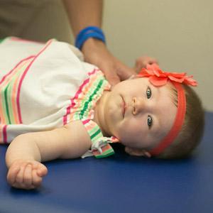 Baby girl laying on adjusting table