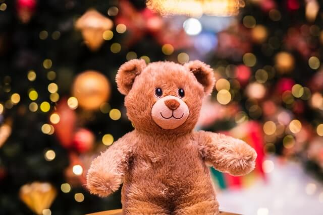 toy bear by christmas tree
