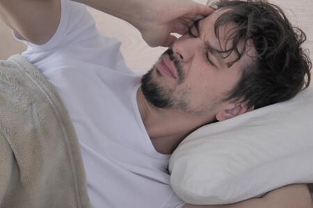 Man waking up with headache