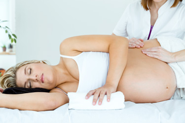 pregnant woman having a massage in spa.