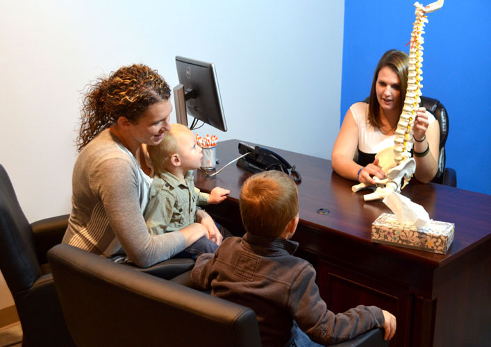 Chiropractor in Clive explains Chiropractic to a family