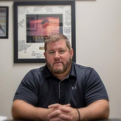 Chiropractor Newington, Dr. Eric sitting at desk