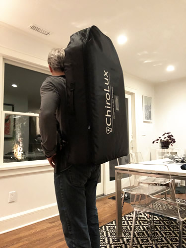 Dr Robert carrying chiro table on his back