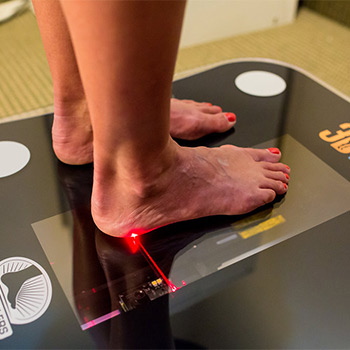 woman getting her feet scanned for custom orthotics